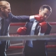Powerful businessman in suit and boxing gloves attacking his rival
